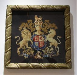 A needlepoint royal coat of arms